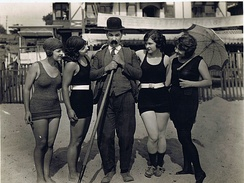 Actor Billy Bevan flanked by four bathing beauties, 1920s