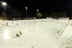 The skaters in yellow vests in the foreground are ball boys at this bandy game.