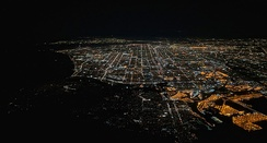 In this night-time aerial photograph of Los Angeles, San Pedro is in the center and right foreground, including part of the brightly lit Terminal Island. The dark peninsula to the left of San Pedro is Palos Verdes.