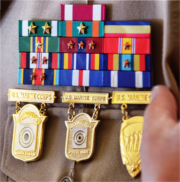 Above are three marksmanship competition badges on a U.S. Marine Corps service uniform; from left to right: Distinguished Marksman Badge, Distinguished Pistol Shot Badge, and the Inter-Division Pistol Competition Badge.