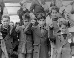 Children preparing for evacuation, some giving the Republican salute. The Republicans showed a raised fist whereas the Nationalists gave the Roman salute.[note 4]