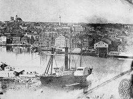 Baltimore harbor in 1849 with the prominent Washington Monument in the background north of the city