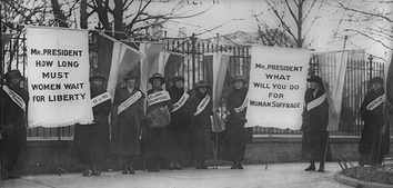 "The Silent Sentinels, women suffragists picketing in front of the White House circa February 1917. Banner on the left reads, ""Mr President, How long must women wait for Liberty?"", and the banner to the right, ""Mr President, What will you do for women's suffrage?""[199]"
