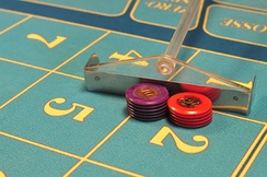 Croupier's rake pushing chips across a roulette layout