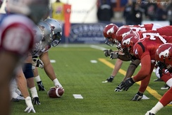 The Montreal Alouettes offensive line (left) and the Calgary Stampeders defensive line (right)