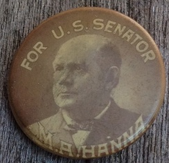 "A late 19th century celluloid political button in black and white; on the top ""For U.S. Senator"" and at bottom ""M.A. Hanna"", framing an image of the candidate"