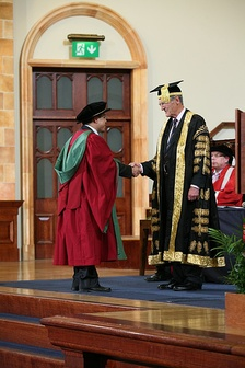 A new PhD graduate from the University of Birmingham, wearing a doctor's bonnet, shakes hands with the Chancellor