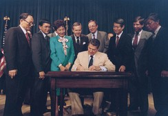 President Reagan signing the Civil Liberties Act with Wilson looking on