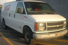 A Chevrolet Express van bearing the logo of The Coca-Cola Company.