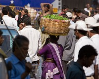 A woman carrying a basket full of vegetables on her head in K R Market, Bangalore, India