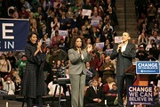 Michelle Obama, Oprah Winfrey and Barack Obama on stage at a campaign rally.
