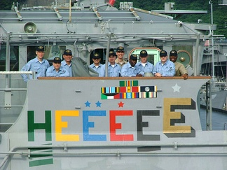 "Crew members aboard the guided missile cruiser USS Chancellorsville (CG-62) assemble on the ship's bridge wing to admire the painting of a gold ""E"". The painted green H is for the Force Health and Wellness Unit Award"