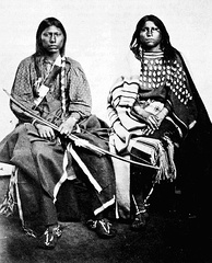 A Kiowa couple. The woman on the right is wearing an elk tooth dress.