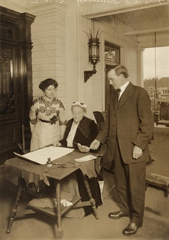 Duniway (seated) with Governor Oswald West, signing the women's suffrage amendment