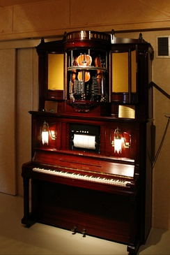 Mechanical piano combined with strings. There are three violins each with only one string. Thus, only tunes that do not require the missing fourth string can be played.