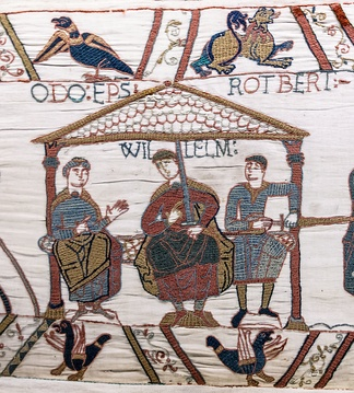 "Robert (Rotbert), Count of Mortain (right) sits at the left hand of his half-brother William, Duke of Normandy. Robert's full brother Odo (Odo Ep[iscopu]s, ""Bishop Odo"") sits to William's right, implying his seniority. This scene in the Bayeux Tapestry occurs near Hastings, immediately before William ordered the building of a castle there, some time before the Battle of Hastings."
