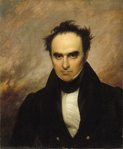 A partially bald black-haired man with large eyes stares directly out of the frame. He is wearing a white shirt, white collar, and black suit.