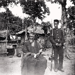 Temne leader Bai Bureh seen here in 1898 after his surrender, sitting relaxed in his traditional dress with a handkerchief in his hands, while a Sierra Leonean Royal West African Frontier soldier stands guard next to him