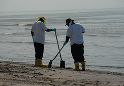 Workers cleaning a beach affected by the spill.
