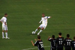 David Beckham scoring with a bending free kick in 2007. The ball is struck with the inside of his right foot, with his body leaning to the left to generate extra curl on the ball.