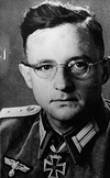 A man with glasses wearing a military uniform with an Iron Cross displayed at the front of his uniform collar.