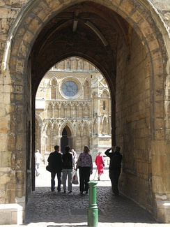The west front of Lincoln Cathedral viewed through the Exchequer Gate, one of a number of surviving gates in the Cathedral Close walls.