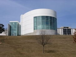 A large white and cement building sits on top of a large hill. A large round part of the building juts out from the rest and contains many windows.