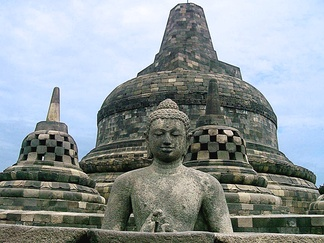 Buddha in an open stupa and the main stupa of Borobudur in the background.