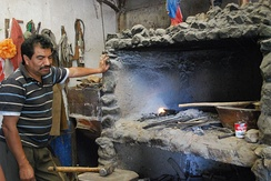 Traditional blacksmith next to his forge of stone and brick