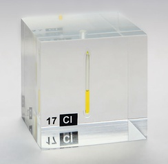 Chlorine, liquefied under a pressure of 7.4 bar at room temperature, displayed in a quartz ampule embedded in acrylic glass.