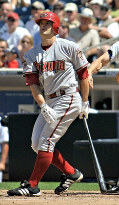 "A man in red socks and a gray baseball uniform with ""Arizona"" on the chest stands after taking a right-handed baseball swing."