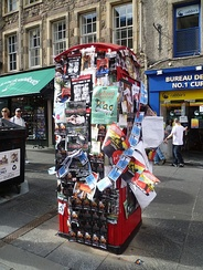Fringe show flyers and posters compete for space on a High Street phone booth