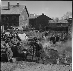 Soviet women having breakfast next to burning trash at a Finnish concentration camp in Petrozavodsk