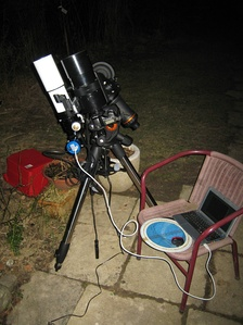 An amateur astrophotography setup with an automated guide system connected to a laptop.