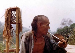 An Akha man smokes a pipe containing opium mixed with tobacco