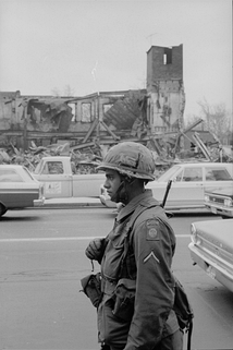 An 82nd paratrooper on guard duty near the passing motorists and the destroyed building on 8 April 1968, during the rioting in Washington, D.C.