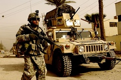 A US soldier on patrol with the support of a Humvee vehicle
