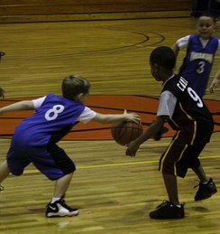 A young defender (left) steals the basketball from an opposing ballhandler