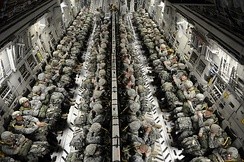 U.S. Army paratroopers seated in a C-17 as it maneuvers to a drop zone for a mass-attack airdrop