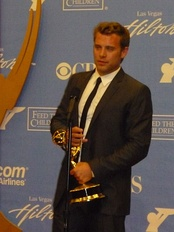 A man with dark hair, wearing a black suit, including a black tie and white T-shirt also holding a gold statuette
