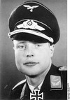 A man wearing a military uniform, peaked cap, and an Iron Cross displayed at the front of his uniform collar.