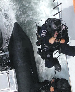 Members of the U.S. Coast Guard Maritime Security Response Team (MSRT) hooking and climbing onto a target to show the skills needed to complete a variety of missions dealing with anti-terrorism, protecting local maritime assets, and harbor and inshore security patrols as well as detecting, stopping, and arresting submerged divers, using the Underwater Port Security System