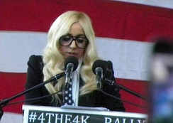 A woman with blonde hair speaking at a podium into several microphones. She wears large glasses. The background is a series of red and white horizontal stripes.