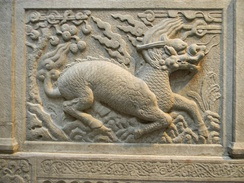 Gilin with the head and scaly body of a dragon, tail of a lion and cloven hoofs like a deer. Its body enveloped in sacred flames. Detail from Entrance of General Zu Dashou Tomb (Ming Tomb).