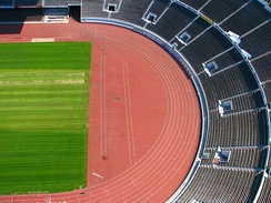 A typical track and field stadium with an oval running track and a grassy inner field