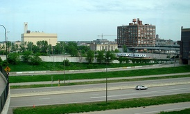 The site of Target Field, two days before construction commenced on May 21, 2007. The location is bordered by 7th St. N (overpass on left), the Hennepin Energy Recovery Center, 5th St. N (overpass on the right side), and the 394 exits and downtown parking ramp (foreground). The tall red building is the Ford Centre.