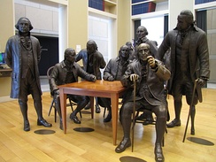 Life-size bronze statue of Benjamin Franklin (seated with cane) in the National Constitution Center, Philadelphia