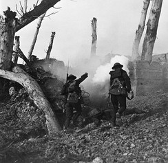 Two British soldiers run toward a bunker past the bodies of two German soldiers.