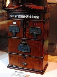 An automatic stamp and postcard vending machine, made by Takashichi Tawaraya in 1904 in Japan.[5]