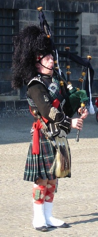 A Pipe Major playing the Great Highland Bagpipe